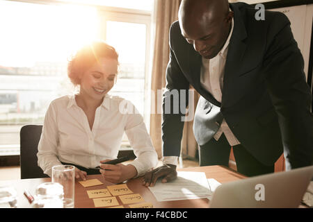 Young business colleagues in conference room discussing manpower resources. Businesswoman sitting with names on - Stock Photo