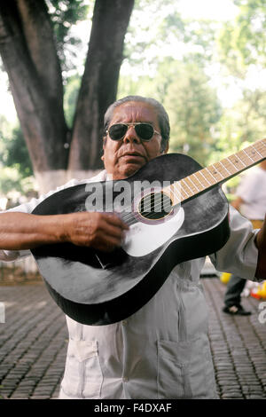 A guitar player performs in the main square of Oaxaca City. Oaxaca City. Oaxaca, Mexico. - Stock Photo