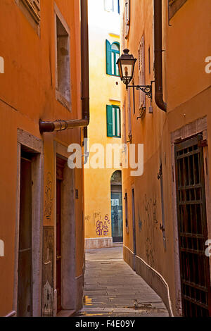 Trieste, Italy - Old town, narrow pedestrian street in the ghetto with lamp street and graffiti - Stock Photo