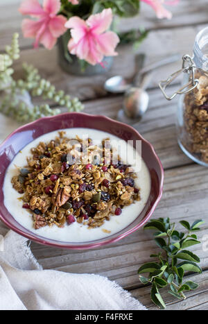 A breakfast setting with a bowl of Spicy Pumpkin, Maple, and Tahini Granola with freshly picked flowers on a farm - Stock Photo