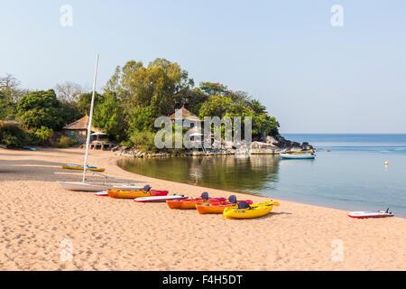 Lakeside beach, Kaya Mawa, with colourful kayak canoes on the sandy shore, Likoma Island, Lake Malawi, Malawi, south - Stock Photo