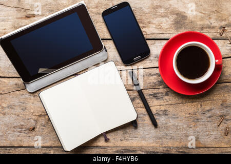 Top view image of workplace. Mock up with tablet PC, notebook, smartphone and cup of coffee - Stock Photo