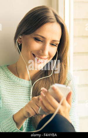 Young smiling woman having fun with listening to music or using her smartphone. Happy beautiful girl relax at window - Stock Photo