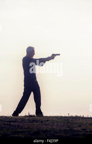 silhouette of a man with a gun - Stockfoto