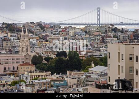 View of San Francisco houses from Russian Hill, Oakland Bay Bridge behind, San Francisco, California, USA - Stock Photo