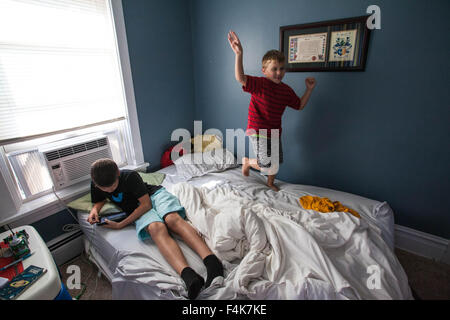 A young boy looks at his tablet while his younger brother annoyingly dances on his bed - Stock Photo