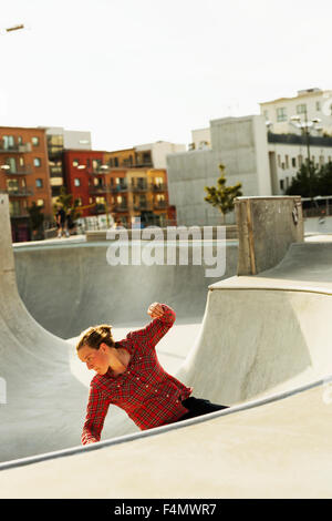 Sporty woman riding skateboard in skate park - Stock Photo