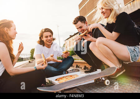 Friends sitting together outdoors sharing a pizza - Stock Photo