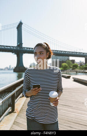 USA, New York City, portrait of smiling young woman with smartphone and coffee to go - Stock Photo