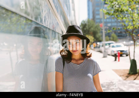 USA, New York City, portrait of young woman wearing black hat - Stock Photo