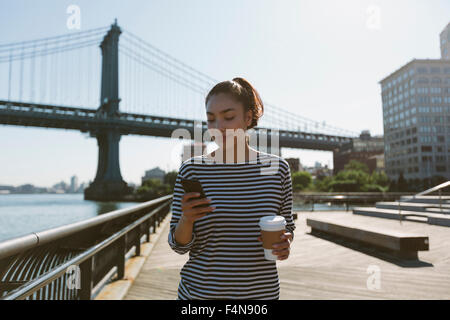 USA, New York City, portrait of smiling young woman with coffee to go looking at her smartphone - Stock Photo