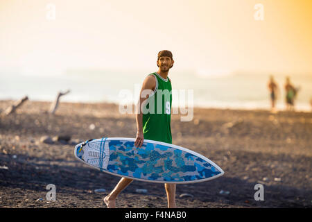 Indonesia, Bali, surfer walking on the beach - Stock Photo