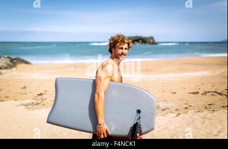 Spain, Asturias, Colunga, smiling surfer walking with bodyboard on the beach - Stock Photo