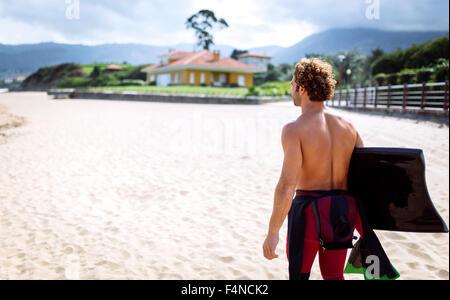 Spain, Asturias, Colunga, surfer walking with bodyboard on the beach - Stock Photo