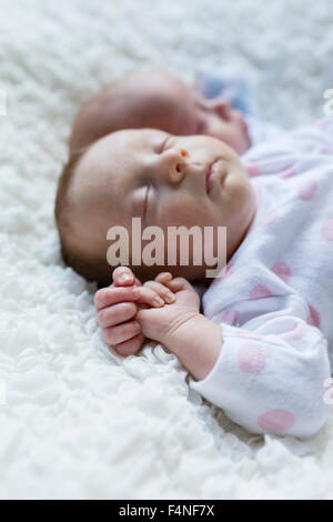 Portrait of sleeping newborn baby girl lying besides her twin brother - Stockfoto