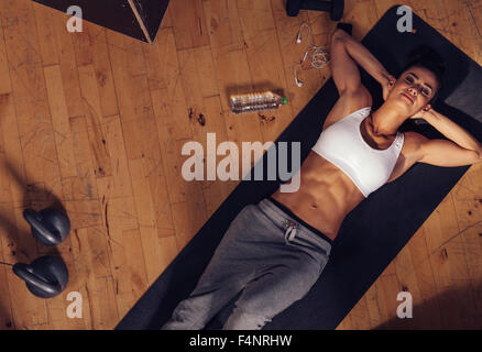 Top view of relaxing young woman lying on fitness mat. Overhead shot of female athlete resting after intense workout - Stock Photo