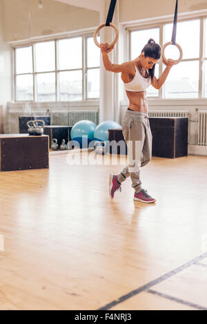 Shot of a thoughtful young woman resting after training session. Fitness female looking down while standing in gym - Stock Photo