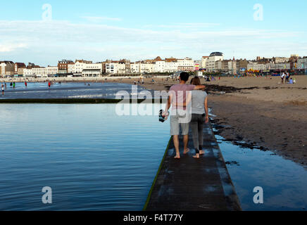 A young couple, with their arms around each other, walk along the wall of the Tidal Bathing Pool, on the beach at - Stockfoto