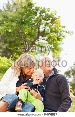 Sweden, Sodermanland, Jarna, Portrait of grandmother and grandfather hugging their grandson (12-17 months) - Stock Photo