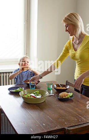Finland, Helsinki, Kallio, Mother putting a glass of water before son at lunch table - Stock Photo