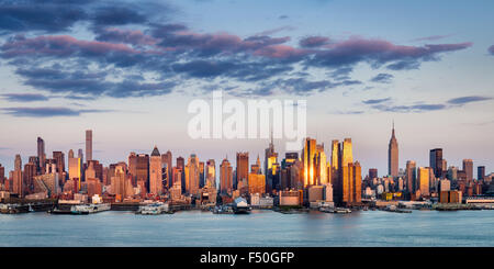 Midtown Manhattan Skyscrapers Reflecting Light at Sunset. New York City panoramic aerial view across the Hudson - Stock Photo