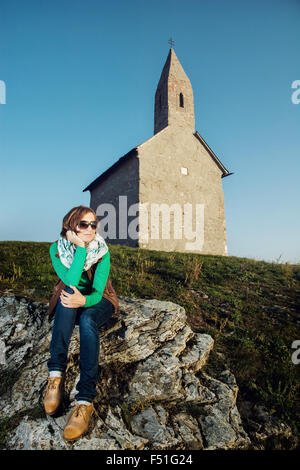 Young caucasian woman is sitting in front of the Archangel Michael church, Slovakia. - Stock Photo