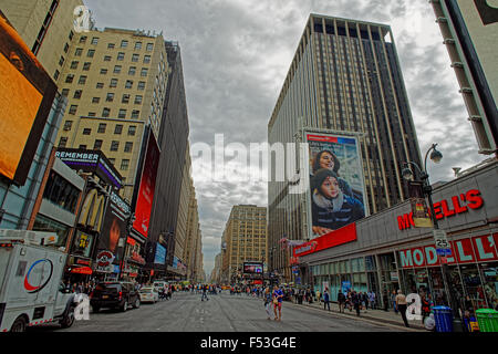 NEW YORK, USA - MAY 06, 2015: Typical New York street view with tall buildings, vehicles and a young couple crossing - Stock Photo