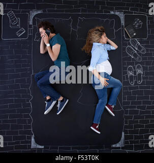 Young couple doing activities in bed. The man is talking on the phone while she is sleeping. - Stock Photo