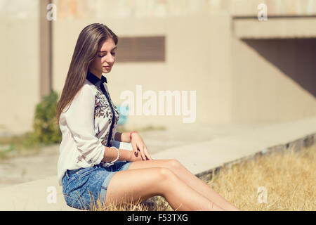 Young hipster girl with long hair sitting on concrete border. Urban portrait of student girl with copy space - Stock Photo