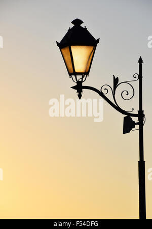 Street antique style lamp post with effect of shine from low light of sunset - Stock Photo