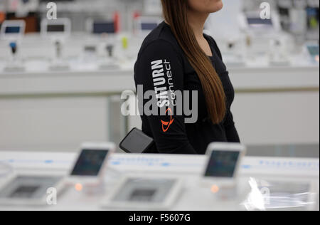 Cologne, Germany. 28th Oct, 2015. An employee in the smartphones and tablets section in a Saturn Connect Markt in - Stock Photo