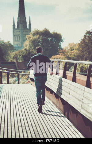 Man running across urban bridge with church in the background - Stock Photo
