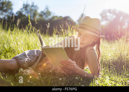 A young girl in a straw hat lying on the grass reading a book. - Stock Photo