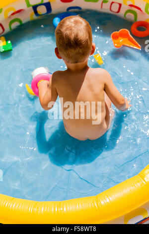 Toddler playing with his toys in a pool outdoors during summertime - Stockfoto