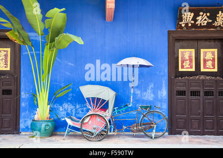 Georgetown, Malaysia — 04 August, 2014: Old rickshaw tricycle near Fatt Tze Mansion or Blue Mansion, famous oriental - Stock Photo