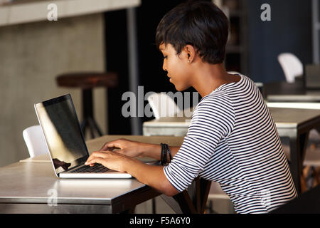 Side portrait of an attractive young african american woman using laptop - Stock Photo