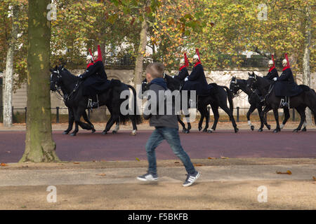 London, UK. 01st Nov, 2015. A boy runs on alongside a troop of Horse Guards riding along on the Mall, London under - Stock Photo