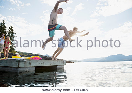 Young men jumping from dock into lake - Stock Photo