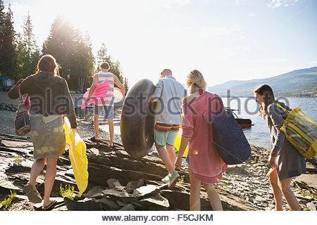 Young friends carrying pool rafts at sunny lakeside - Stock Photo