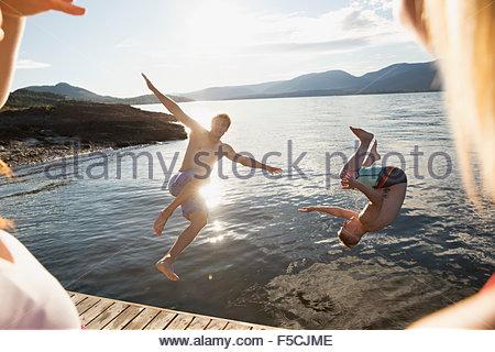 Young women watching men jump into lake - Stock Photo