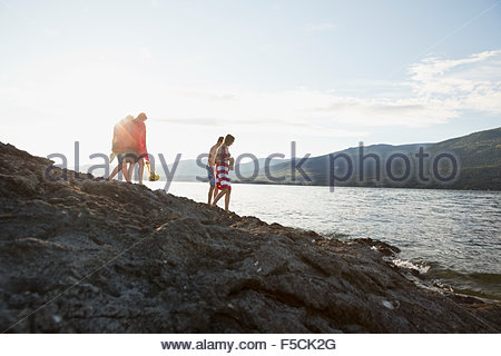 Young friends walking on rocks at sunny lake - Stock Photo
