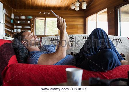 Man laying on cabin sofa using digital tablet - Stock Photo