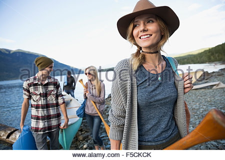 Smiling young friends with canoe at lakeside - Stock Photo