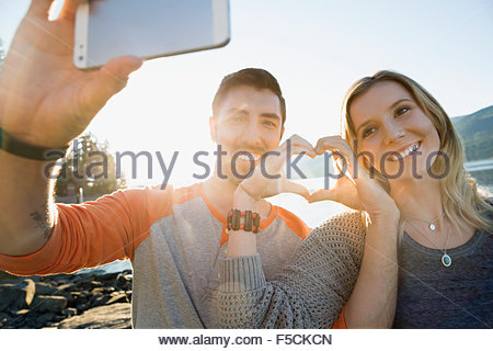 Young couple forming heart-shape with hands lakeside - Stock Photo