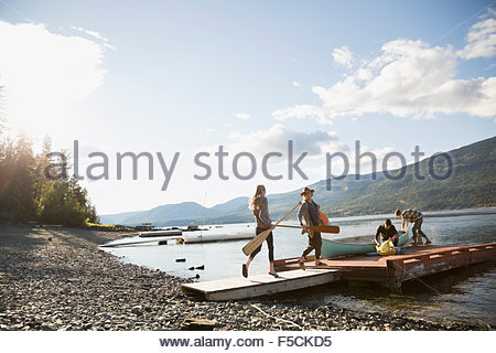 Young friends canoe and paddles on lake dock - Stock Photo