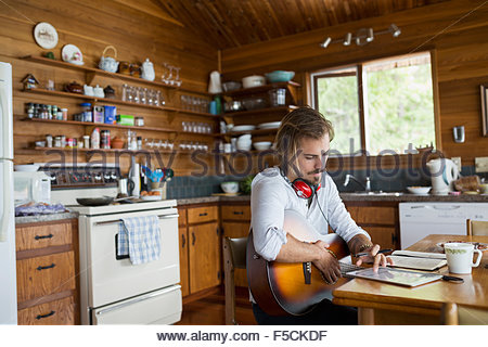 Man with guitar digital tablet songwriting cabin table - Stock Photo