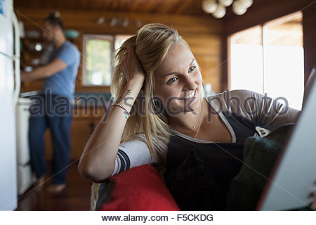 Young woman using digital tablet on cabin sofa - Stock Photo