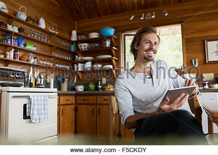 Smiling man using digital tablet cabin kitchen table - Stock Photo