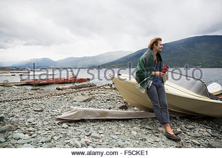 Man drinking coffee against boat at lakeside - Stock Photo