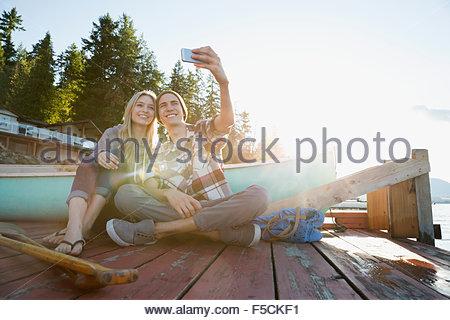 Smiling young couple taking selfie dock near canoe - Stock Photo